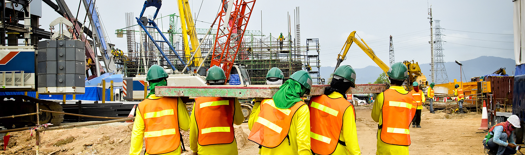 Construction Insurance: Builders lifting something together on a worksite