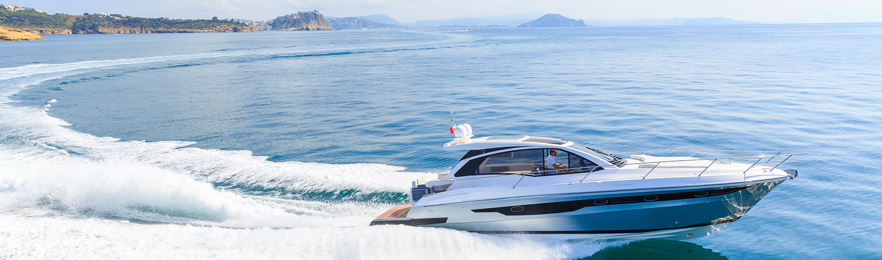 High Net Worth Insurance: A man driving a private boat across the sea