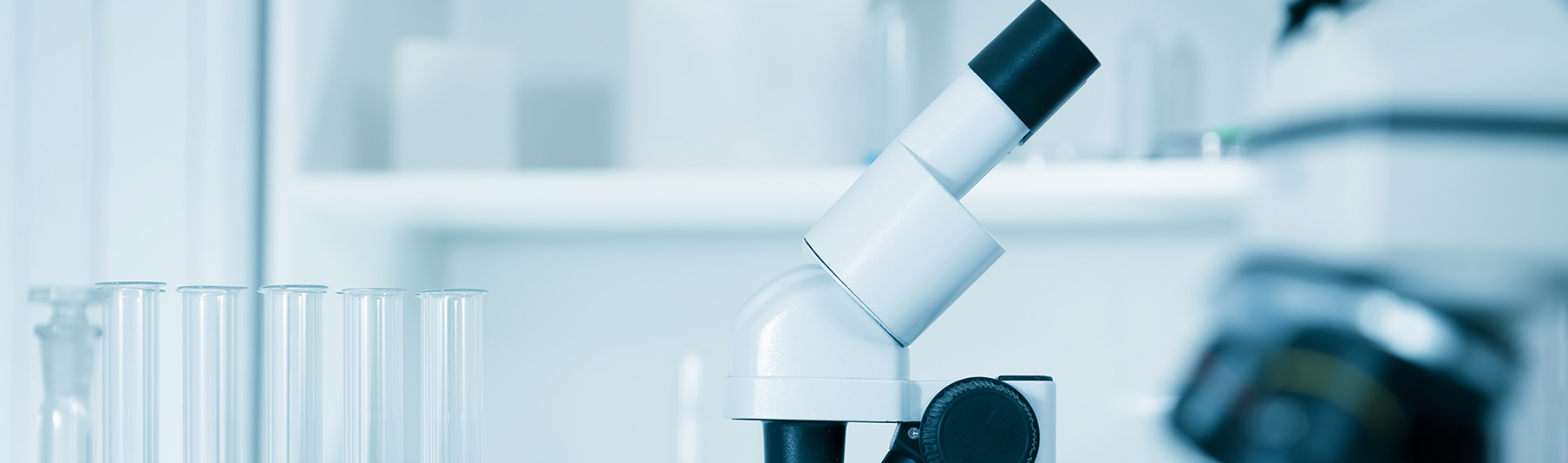 Medical Technology Insurance: A microscope next to a row of beakers