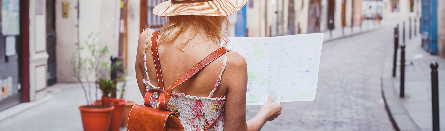 Travel Insurance: A woman on holiday looking at a map while walking the streets